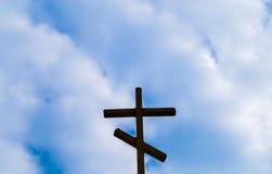 Religion wooden cross against the blue sky. Symbol Stock Image