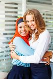 Religions friendship. Muslim and christian girls hugging Royalty Free Stock Photography