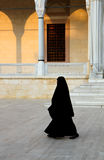 Religios Muslim Woman Walking. Religious muslim woman with black burka walking in front of the local mosque in Adana,Turkey royalty free stock photography