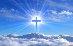 Religioso cruce sobre las nubes de cúmulo iluminadas por los rayos de la resplandor santa, concepto imagen de archivo