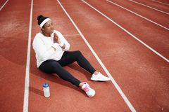 Talk to God. Religious and active plump female in sportswear asking Lord to bless her for workout while sitting on racetrack of stadium Stock Image
