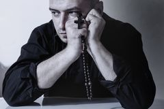 Religious adult man praying with rosary beads.  stock photos