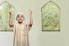 Religious asian muslim child standing praying to god Stock Image