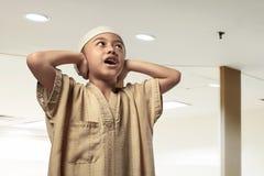 Religious asian muslim kid with cap praying Stock Photo