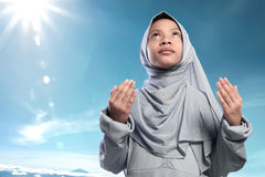 Religious asian muslim kid raising hand and praying Royalty Free Stock Image