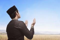 Religious asian muslim man with black cap praying Royalty Free Stock Photos
