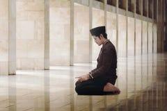 Religious asian muslim man with black cap praying Stock Image