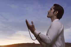 Religious asian muslim man holding prayer beads and praying Royalty Free Stock Images