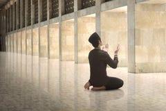 Religious asian muslim man raising hand and praying Stock Photo