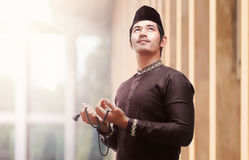 Religious asian muslim man in traditional dress using prayer bea Royalty Free Stock Image