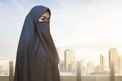Religious asian muslim woman with covered face standing. Against cityscape background Stock Photos