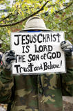 Religious belief. A person holding a Religious belief sign dressed in camouflage clothing and hiding behind the message Stock Image