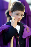 Religious Boy. A candid headshot view from a young religious boy wearing a purple costume and holding a wooden stick during an Easter Procession in Portugal Royalty Free Stock Images