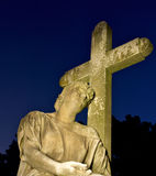 Religious Cemetary Headstone. Cemetary headstone of a man resting his head against a cross surrounded by a dark blue night sky Royalty Free Stock Image