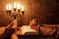 Religious female crossed hands in prayer with bible and candle. Religious Christian man and woman praying over Bible indoors royalty free stock photo