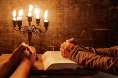 Religious female crossed hands in prayer with bible and candle. Religious Christian man and woman praying over Bible indoors royalty free stock photography
