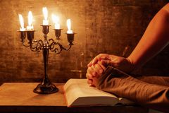 Religious female crossed hands in prayer with bible and candle. Religious Christian man and woman praying over Bible indoors royalty free stock image
