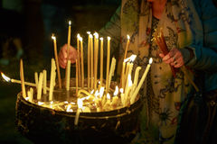 Religious Christian woman lights a candle in the Holy Sepulchre on Mount Calvary Royalty Free Stock Image