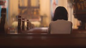 Religious Christian woman praying in church. Back view of religious Christian woman sitting in the church while praying to GOD. Shot in 4k resolution stock footage