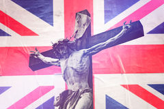 Religious Concept, Christianity in United Kingdom. With Jesus Christ Crucifixion against United Kingdom Flag, Retro Toned Effect Stock Photo