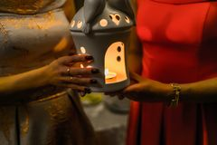 Religious concept. Two females hands holding a burning candle in. Candlestick Stock Photography