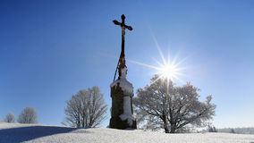 Religious crisis in the winter landscape lit. Midday sun. Bohemian Forest, Sumava, winter, Czech Republic Royalty Free Stock Photo