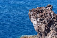 Religious cross on a cliff against blue water of Atlantic ocean. Madeira island, Portugal royalty free stock image