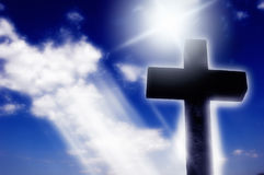 Religious cross in Light. Religious cross in silhouette in front of a blue sky with divine lights Stock Image