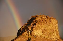 Rainbow and golden rock on Gran Canaria. Religious cross on mountain during dramatic weather on Grand Canary royalty free stock image