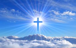 Religious cross over cumulus clouds illuminated by the rays of holy radiance, concept. Religious cross over cumulus clouds illuminated by the rays of holy stock image
