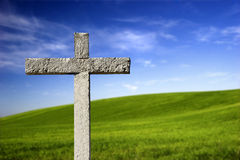 Religious cross in the paradise. Religious stone cross on a beautiful green hill Royalty Free Stock Images