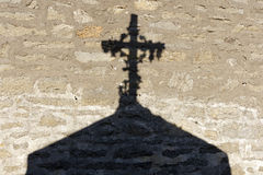 Religious cross shadow. Shadow of christian cross on granite wall in brittany, france stock photo