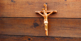 Religious crux handcrafted in clay over some wood wall Royalty Free Stock Photography