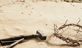 Religious Easter background with crown of thorns. A large old iron nail and small hammer on sand with copy space stock images
