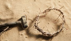 Religious Easter background with crown of thorns. Religious Easter background with a natural twisted crown of thorns together with a hammer and old iron nail royalty free stock photography