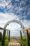Religious entrance with arch against the sky with clouds.  Stock Photography