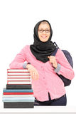 Religious female student leaning on stack of books. Religious female student leaning on a stack of books isolated on white background Stock Photos