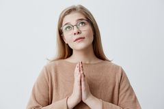 Religious girl with blonde hair in stylish eyewear pressings palms together and looking upwards, praying to God, begging. Religious girl with blonde straight Stock Image