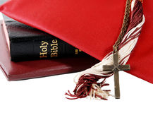 Religious graduation. Mortarboard with tassel, diploma, bible and cross - for a religious graduation theme, isolated on white royalty free stock photo