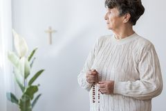 Religious grandmother praying in church Royalty Free Stock Photography