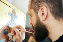 Religious icon painting process. Religious icon painter man paints a new icon with brush at workshop Stock Images