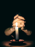 Hands and candle. Prayer, mercy, faith concept. Stock Photos