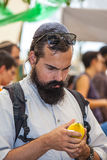 Religious Jew  examines ritual citrus. JERUSALEM, ISRAEL - OKTOBER 8, 2014: Traditional market before the holiday of Sukkot.  Religious Jew with black beard very Stock Image
