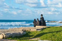 Religious Jew family sitting on the coast of Mediterranean sea in Israel and watching the waves. Sunset beach, family rest traditi. On. Selective focus, space Royalty Free Stock Images