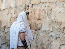 Religious Jewish young man reads prayers outside the fortress walls of the old city of Jerusalem, Israel stock image