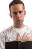 Religious Man. A religious man is reading an old bible while holding one hand over his heart, isolated against a white background Stock Photo
