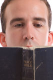 Religious Man. Closeup view of a young man reading an old bible, isolated against a white background Stock Images
