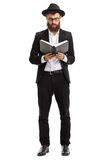 Religious man reading a book. Full length portrait of a religious man reading a book isolated on white background Royalty Free Stock Image