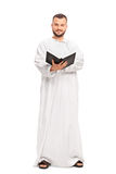 Religious man in a white robe holding a holy book Stock Photo