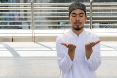 Religious muslim man praying in city Stock Photo